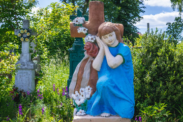 Statue of a girl under the cross on a cemetery in Chortkiv, Ukraine