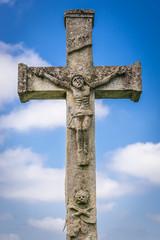 Stone cross on abandoned Catholic cemetery near Chervonohorod Castle ruins in Ukraine