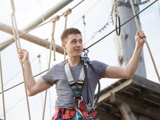 junger Mann klettert im Hochseilgarten