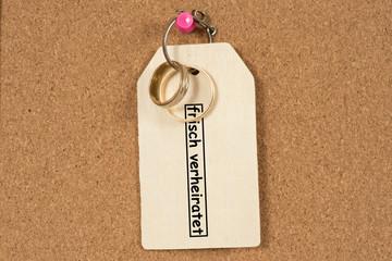 Zwei Eheringe, ein Schlüssel und ein Schild mit dem Text Frisch Verheiratet