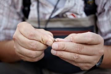 Hands of a fisherman preparing utensils