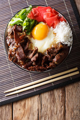 Gyudon beef with rice, egg and onion closeup in a bowl on the table. Vertical top view