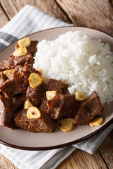 Philippine beef Salpicao with rice garnish closeup on a plate. vertical