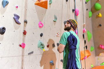 Kletterer vor einer Wand mit Kletterseil in einer Sporthalle // Climber in front of a wall with climbing rope in a sports hall