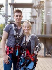 fröhliches Pärchen hat Spaß im Kletterpark und trägt Sicherheitsausrüstung zum Sichern beim klettern