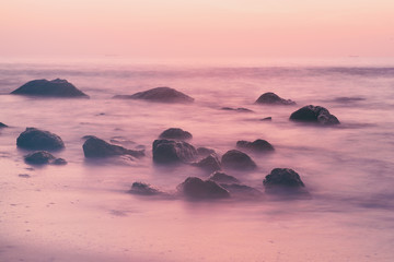 Summer seasonal natural vacation background. Romantic morning at sea. Big boulders sticking out...