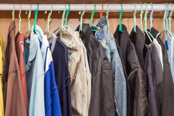 The clothes hang on rail in wooden cabinet,wood cupboard