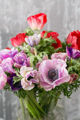 bouquet of mixed anemones flowers in vase . the work of the florist at a flower shop.