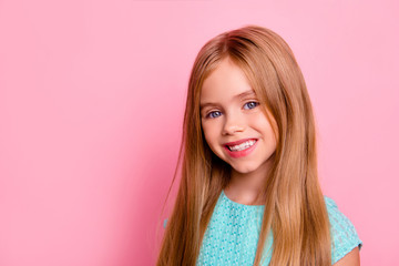 Close up portrait of cute lovely beautiful healthy little girl with long smooth straight blonde hair, blue eyes, wearing blue dress, isolated on bright pink background, copyspace