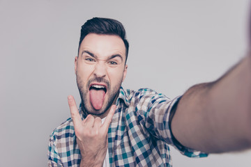 Self portrait of  attractive, crazy man with bristle, stubble, shooting selfiye and showing rock and roll symbol with tongue out to the front camera over grey background