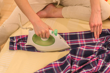 Young woman stroking a plaid shirt with an steam iron