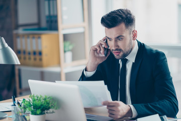 Portrait of attractive professional brunet wondered accountant with bristle in blue jacket holding monthly report, looking at document, talking on smart phone in workstation, sitting at his desktop