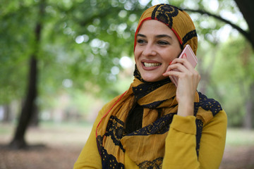 Young Muslim woman talking with smart phone.