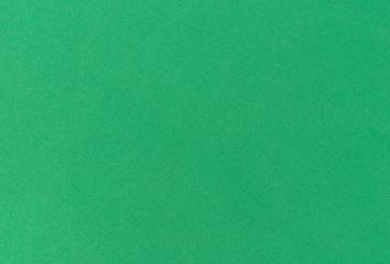 Close view of a festive bright green foam background.