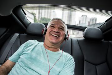 Happy senior man listening music in the car