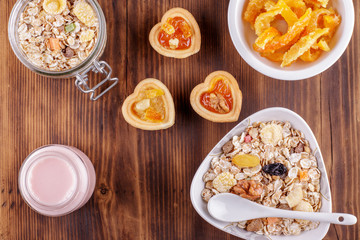 Healthy breakfast. Ceramic bowl with oat flakes, dried fruits, nuts on wood background