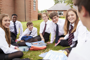 Teenage Students In Uniform Working On Project Outdoors