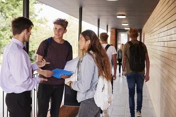 Teenage Students Talking To Teacher Outside School Buildings