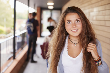 Portrait Of Female Teenage Student On College With Friends