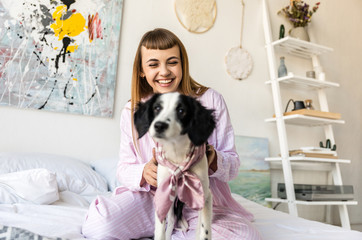 selective focus of smiling woman in pajamas and adorable puppy in bed at home