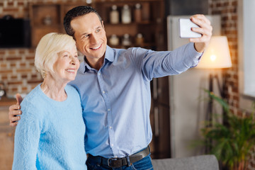 Capturing memories. Handsome young man and his pleasant elderly mother standing together in the middle room and taking a selfie