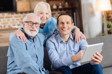 Happy together. Cheerful young man sitting on the couch next to his elderly father and holding a tablet while his mother hugging them from behind, all of them smiling at the camera
