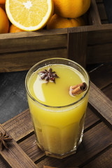 Winter hot drink from oranges and spices on a black background