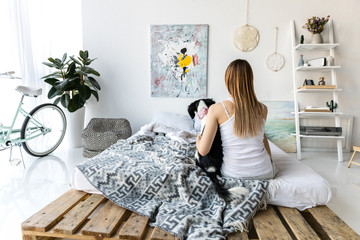 back view of woman and little puppy sitting on bed together at home