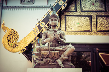 warrior in buddhist temple with golden arquitecture. thailand. chiang mai.