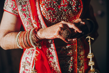 Tender hands of an Indian bride covered with henna tattoo while she dressed in red lehenga with golden embroidery