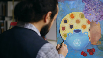 Close-up of Skilled artist man teaching and showing the basics of painting in art studio