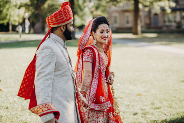 Indian groom dressed in white Sherwani and red hat with stunning bride in red lehenga stand and hold each other tender while they walk