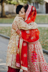 Man hugs beautiful Indian bride in red lehenga and veil embroidered with gold