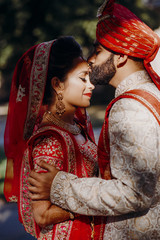 Indian groom dressed in white Sherwani and red hat with stunning bride in red lehenga stand and hold each other tender while they kiss in the lights of sun