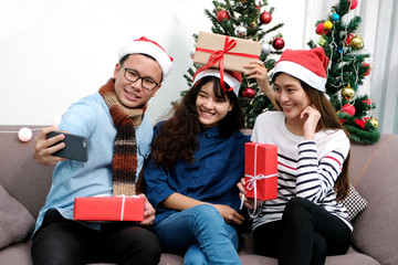 Young asia man and women holding gift boxes taking photo with happiness in Christmas party, friends Christmas party celebration