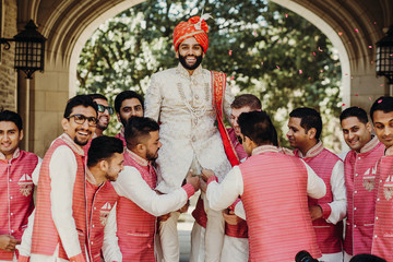 Handsome Indian groom in white sherwani and red hat sits on the shoulders of his groomsmen outside