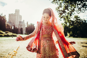Stunning Indian bride dressed in Hindu traditional wedding clothes lehenga embroidered with gold and a veil smiles tender posing outside with golden accessories