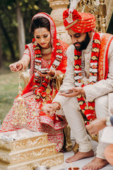 Indian bride and groom dressed in traditional shewrani, lehenga and with flower garlands on their necks sit on the chairs and burn fire during Hindu wedding ceremony