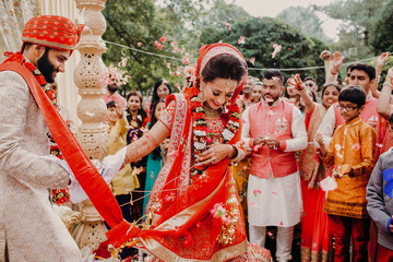 Indian groom dressed in white Sherwani and red hat with stunning bride in red lehenga during the Saptapadi ceremony on Hindu wedding