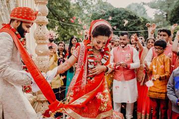 Indian groom dressed in white Sherwani and red hat with stunning bride in red lehenga during the Saptapadi ceremony on Hindu wedding