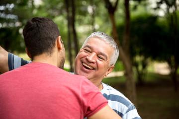 Adult son hugging his senior dad