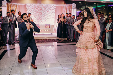 Indian groom in classy western suit and bride in pink Hindu dress dance in the restaurant hall