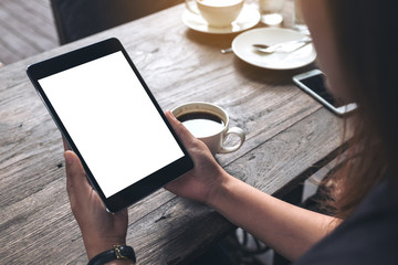 Mockup image of business woman's hands holding black tablet pc with blank white screen and coffee cup on vintage wooden table in cafe background