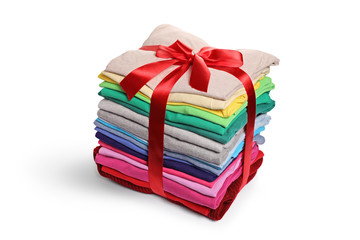 Stack of ironed and packed clothes wrapped with a red ribbon as a present