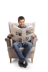 Young man sitting in an armchair and reading a newspaper