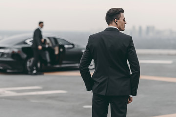 rear view of bodyguard in suit and sunglasses