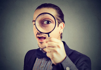Curious business man looking through a magnifying glass