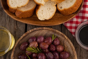 Overhead view of olives and bread with oil in container