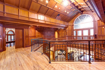 Second floor landing accented with wood paneled walls and ceiling.