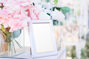 Blank  frame on the table and flower decoration